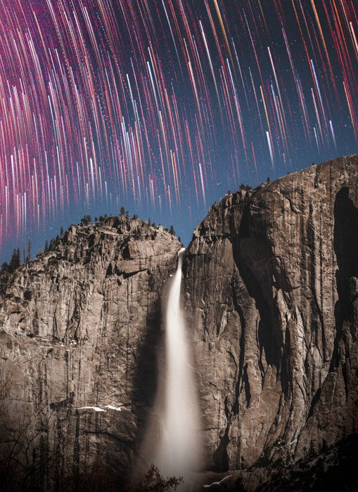 Stunning time lapse photography of pink light trails over a misty gushing waterfall