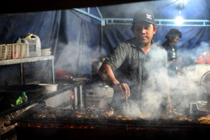 Street photography of a man cooking on a grill inside a tent- travel photography checklist.