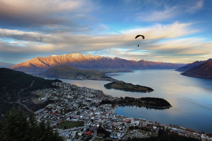 Wide angle photo of a beautiful coastal landscape with a paraglider - travel photography checklist