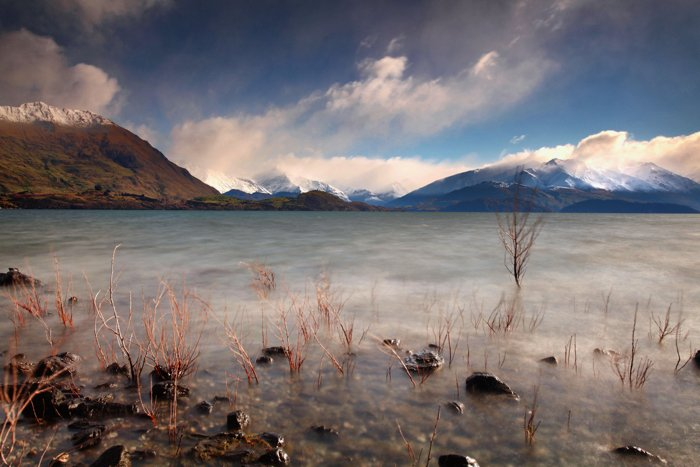 Long exposure photography of water in the foreground of a mountainous landscape - travel photography checklist