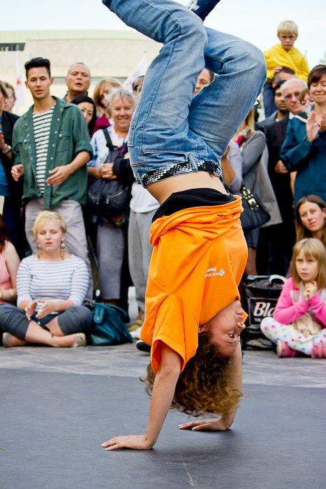Photo of a person doing a handstand in front of a crowd of people.