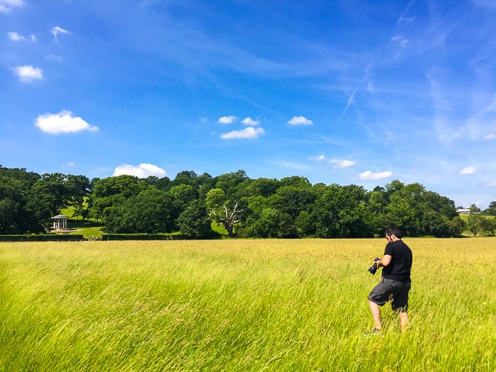 A photographer in a countryside field on a bright sunny day.