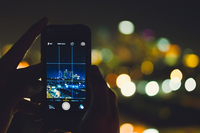 A person shooting street photography at night with a smartphone