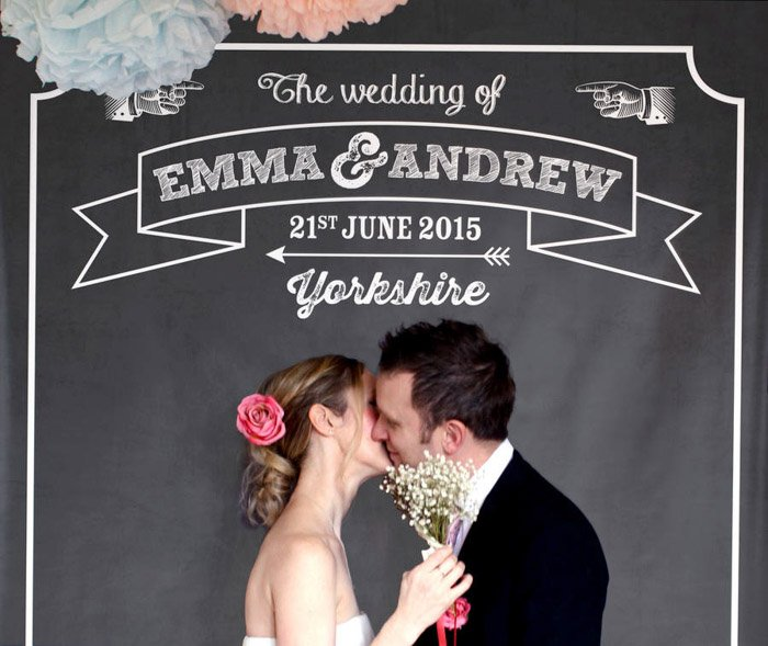 an image of a newly wed couple kissing against a chalkboard photo booth