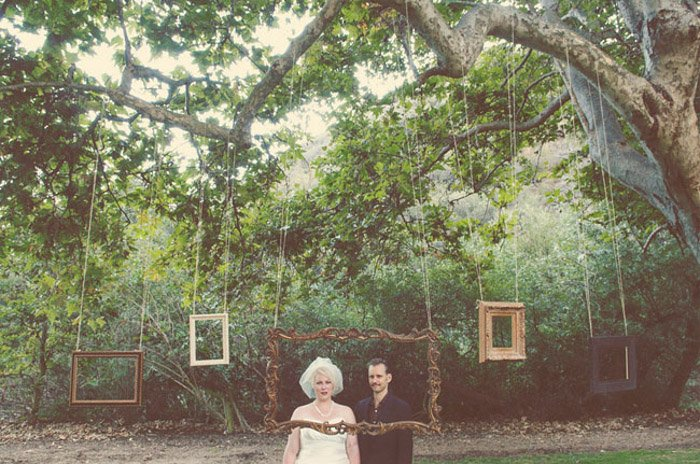 A cool wedding photo booth set up outdoors with various sized photo frames hanging from a large tree branch