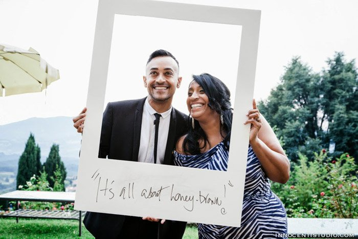 an image of a wedding couple using a large Polaroid Frame as a photo booth