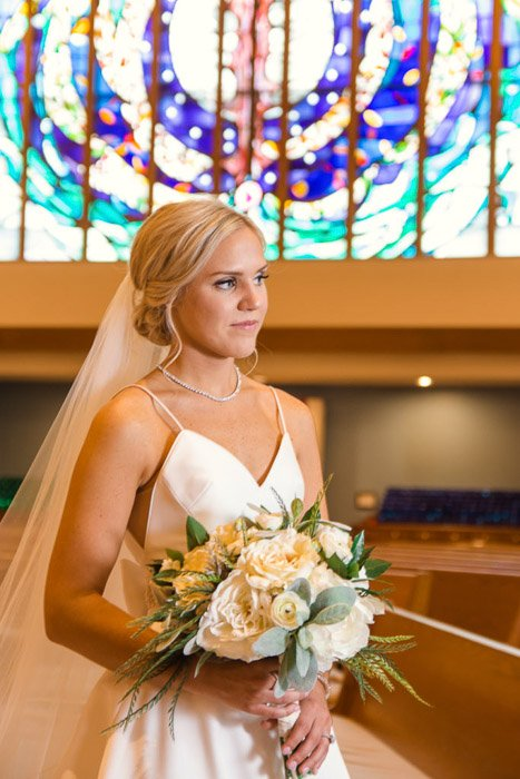 A portrait of the bride holding flowers in the church - photography lights
