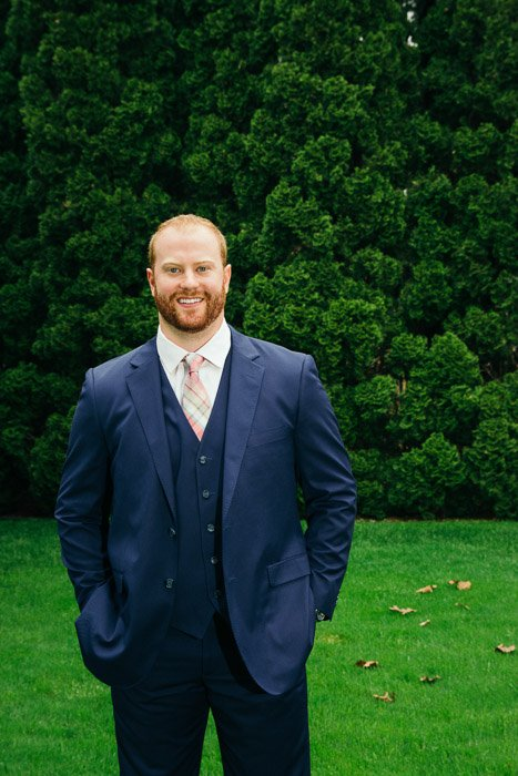 A photo of the groom posing in garden - natural wedding photography lighting