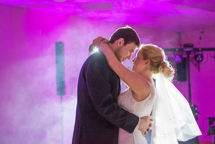 A newlywed couple dancing against purple light - wedding photography light