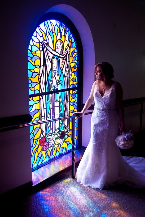 A photo of the bride posing by a large stained glass window - natural wedding photography lights