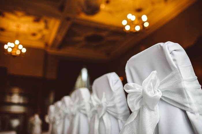 A row of chairs decorated for a wedding ceremony.