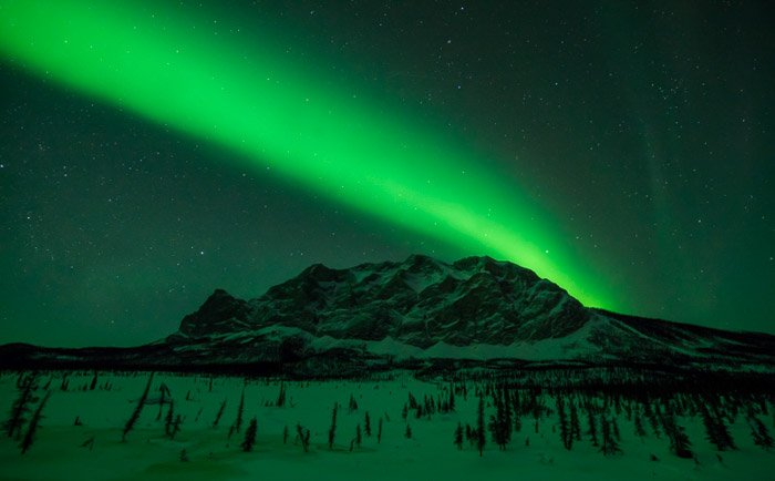 Photo of the northern lights over a mountainous landscape. Winter photography.