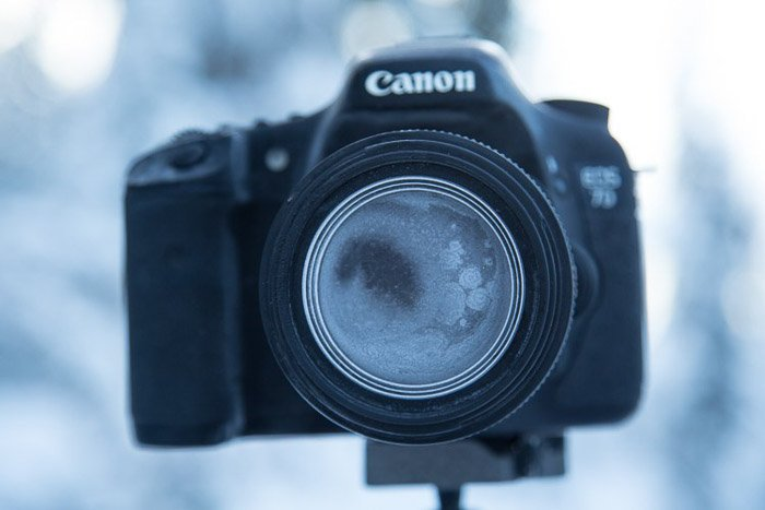 Canon camera on tripod with lens and camera body completely covered in frost, winter photography.