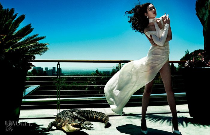 Mario Testino vogue photo shoot of a female model standing on a balcony beside a crocodile