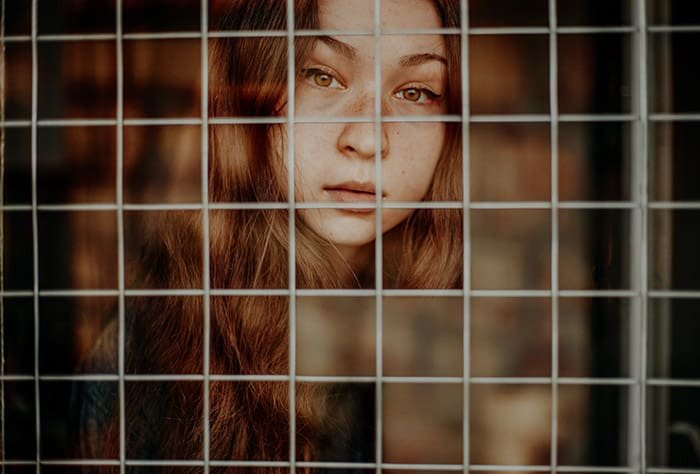 A cut out photo portrait of a brown haired girl behind a chain fence