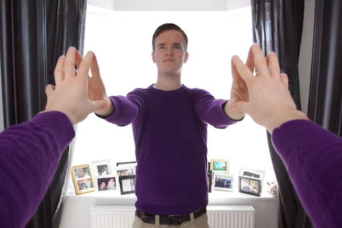 A man in purple jumper touching hands with his reflection in the mirror