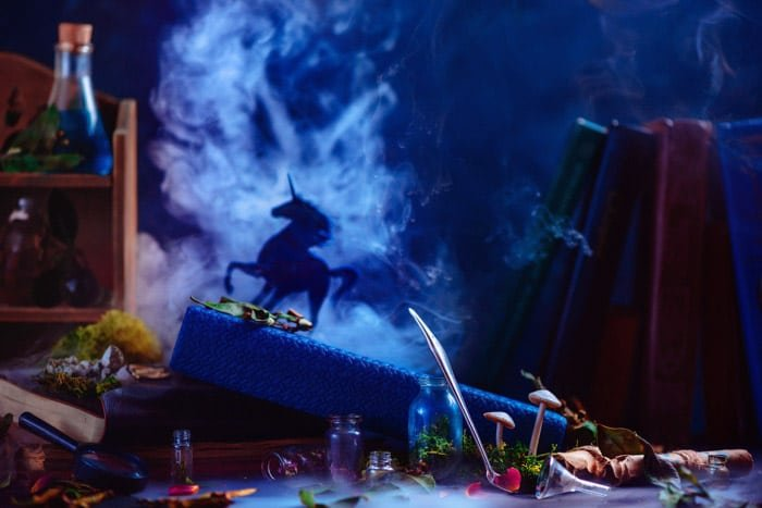 A still life smoke photography featuring glass bottles with the silhouettes of a unicorn and billowing smoke behind