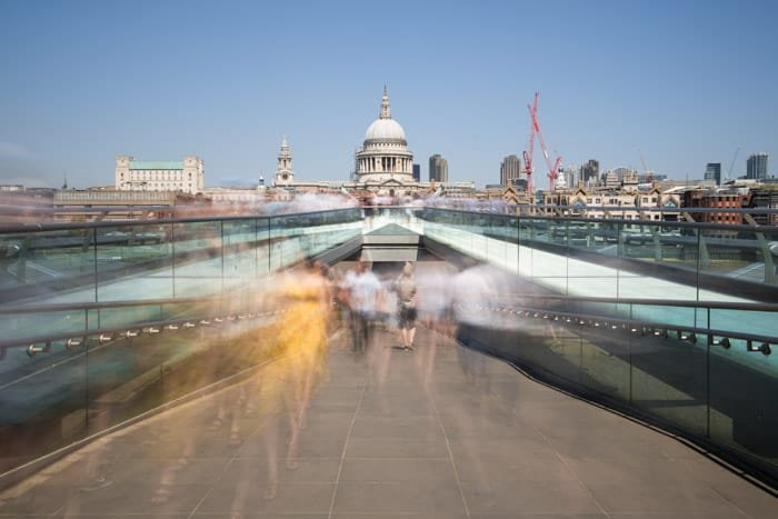 A time lapse photography shot of the blurred figures of people walking out of an underground passage