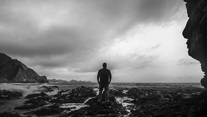 Monochrome coastal photography shot of a man standing on rocks looking towards the ocean using 16:9 aspect ratio