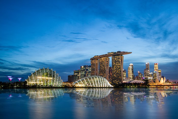 Cityscape shot at the blue hour with buildings at the side of a lake or river