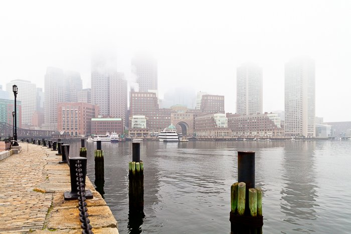 A misty city photography shot taken from the side of a river