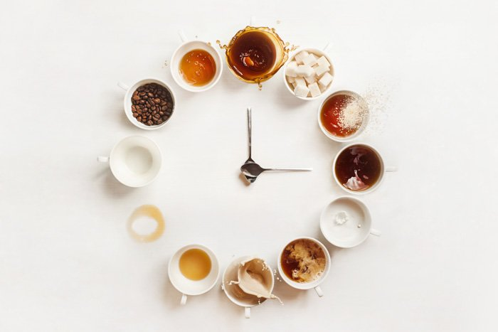 Overhead still life shot of a circle of coffee cups and two teaspoons in the centre acting as clock hands