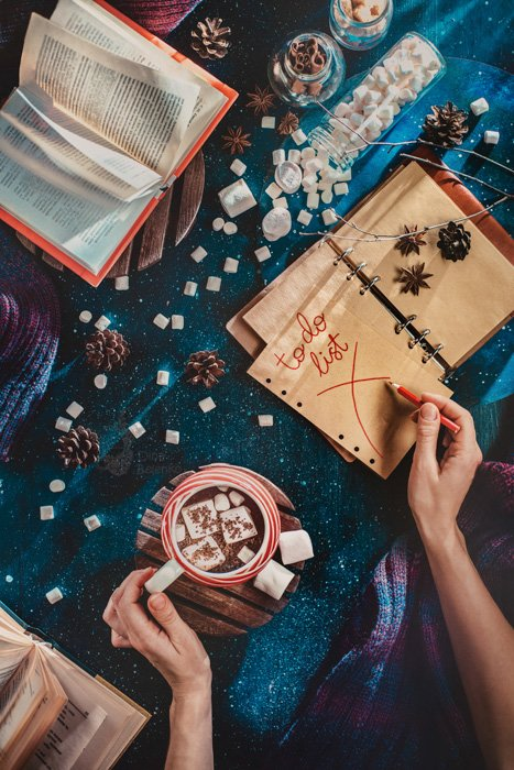 Overhead mystical shot of a person writing a 'to do' list in a notebook while holding a cup of coffee, sugarcubes, pine cones and other props are strewn around a glittery blue background