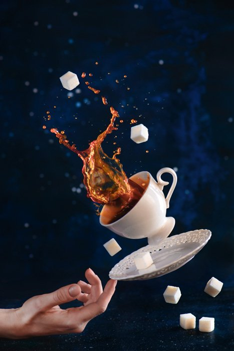 Fun coffee photography shot of a falling cup, saucer and sugar cups balanced on the tip of someones finger