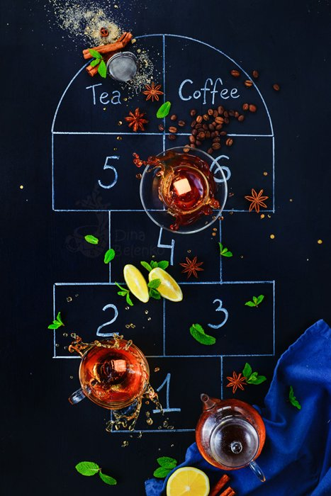 An overhead creative coffee photo shot of the game hopscotch created with coffee cups, cinnamon sticks and spoons