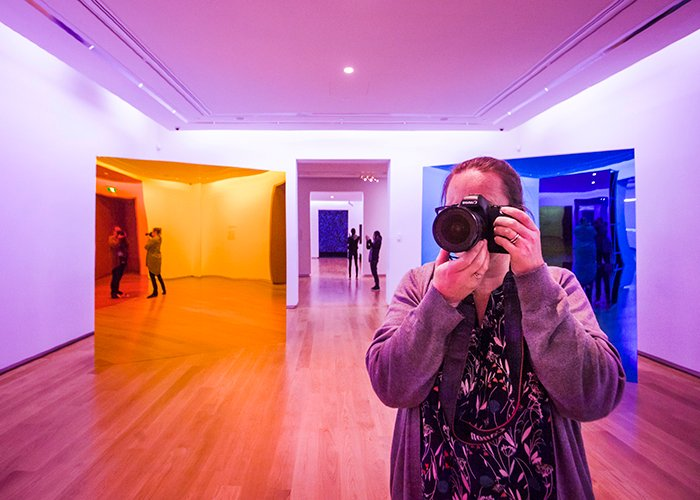 A photographer points the camera towards the camera in an art gallery setting - using color in photography