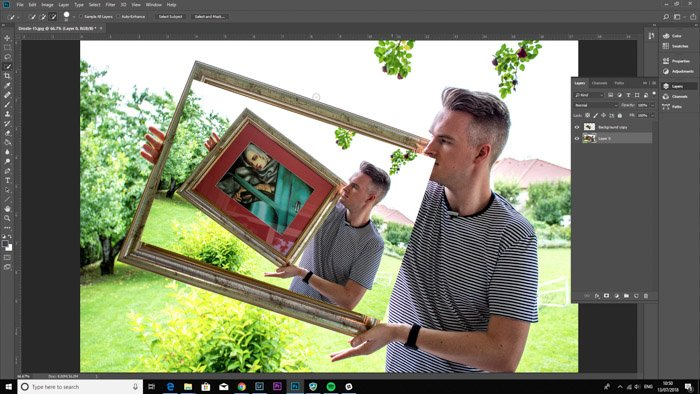 Screenshot of Photoshop editing a photo of a man holding a framed painting - droste-effect step four