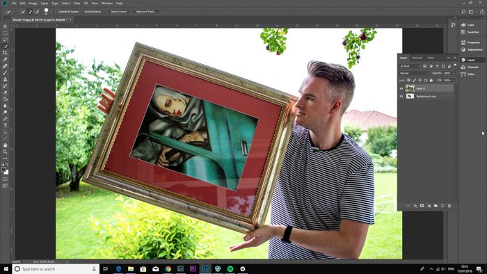 Screenshot of Photoshop editing a photo of a man holding a framed painting - droste-effect step seven