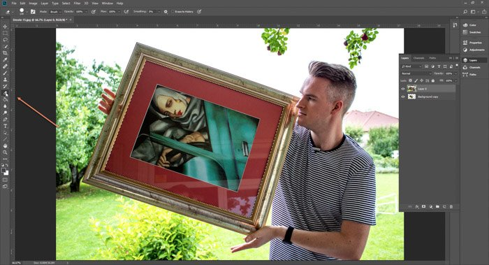 Screenshot of Photoshop editing a photo of a man holding a framed painting - droste-effect step eight