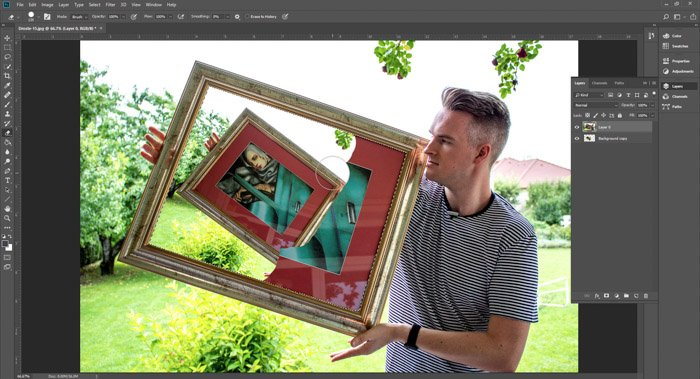 Screenshot of Photoshop editing a photo of a man holding a framed painting - droste-effect step nine
