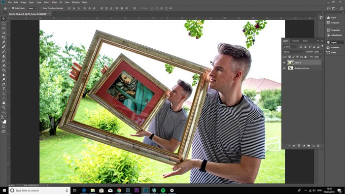 Screenshot of Photoshop editing a photo of a man holding a framed painting - droste effect step ten