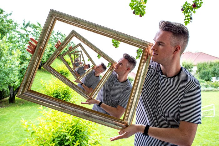The final droste effect image of a man appearing to hold a photo within a photo within a photo