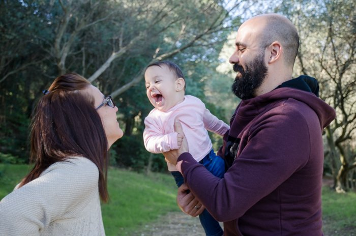 Casual lifestyle family portrait of a couple holding a small baby - family photos composition tips