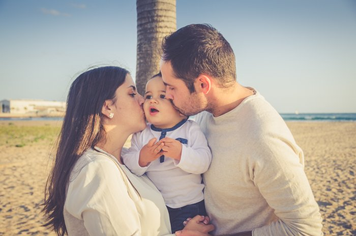Sweet portrait of a man and woman holding a small baby and kissing his cheeks on a beach - family portraits composition