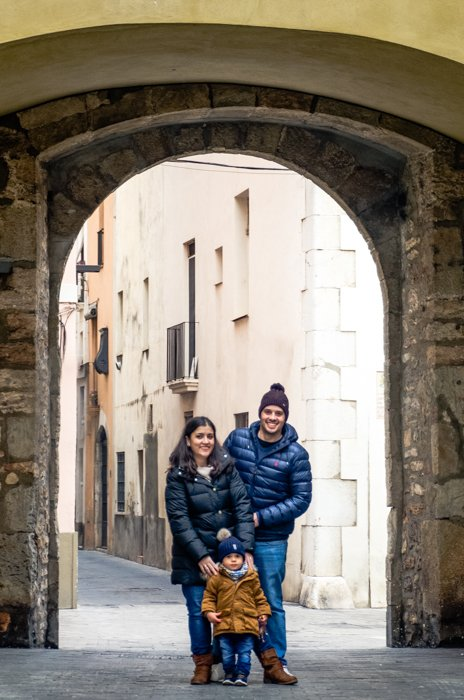 Cute family portrait of a couple with a small baby posing under an arch