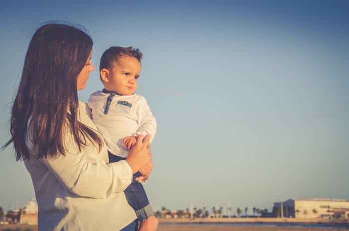 Dreamy low light portrait of a woman holding a small baby on a beach - family portraits composition
