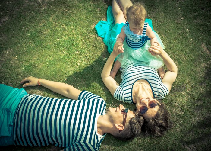 Overhead portrait of a woman holding a small baby and man lying beside her on the grass- composition for family portraits