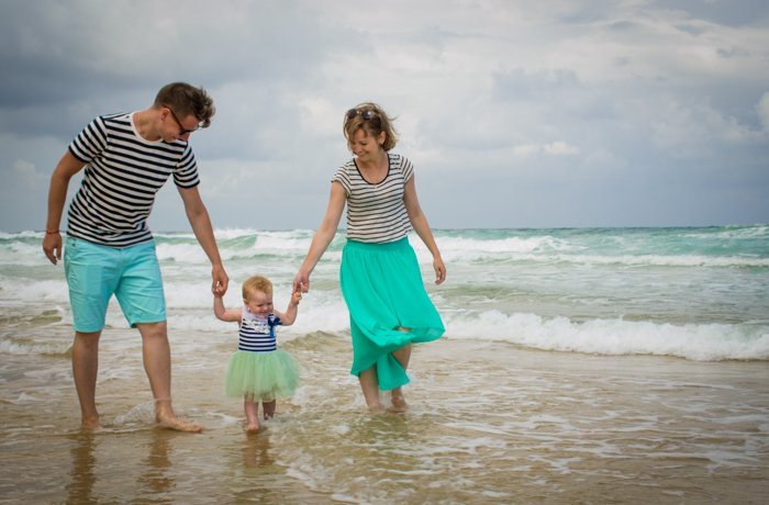 Casual shot of a couple holding a small baby on a beach - family portraits composition