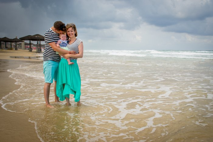 A couple with a small baby posing on a beach - composition tips for family photography.