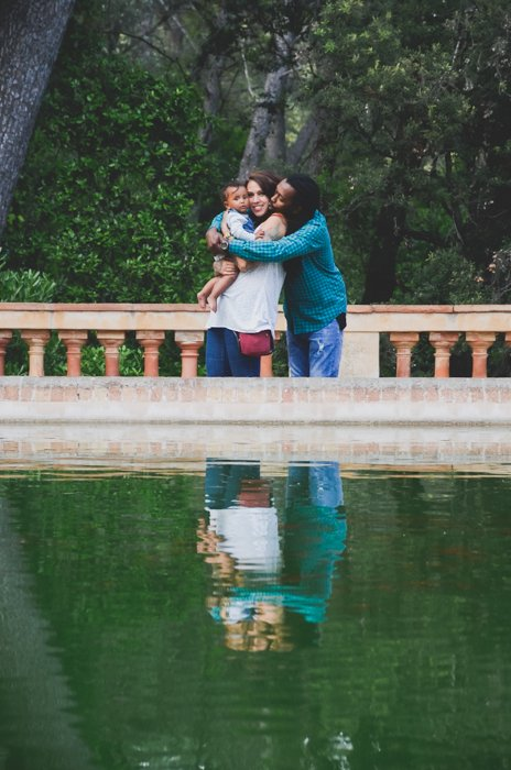 A couple with a small baby posing in front of a pond - composition for family picture ideas