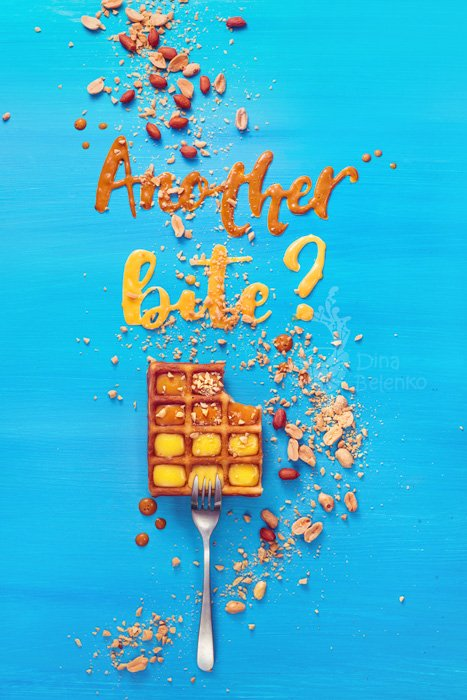 Belgian waffle on a fork with lettering on a sky blue background, Letters written with caramel and peanut sauce - food art example.