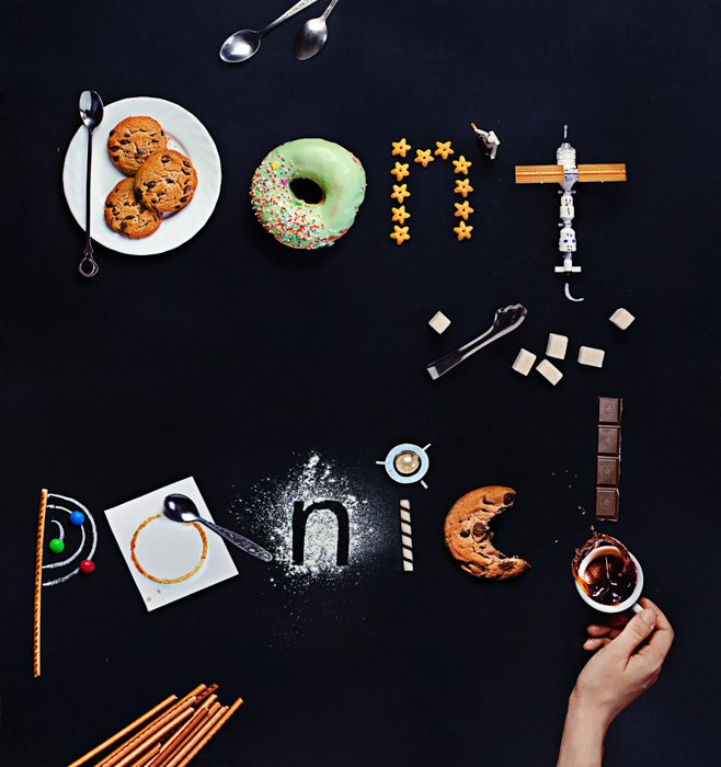 An overhead shot featuring coffee cups, cutlery, toys,saucers, biscuits and other food art props with food typography message 'don't panic'