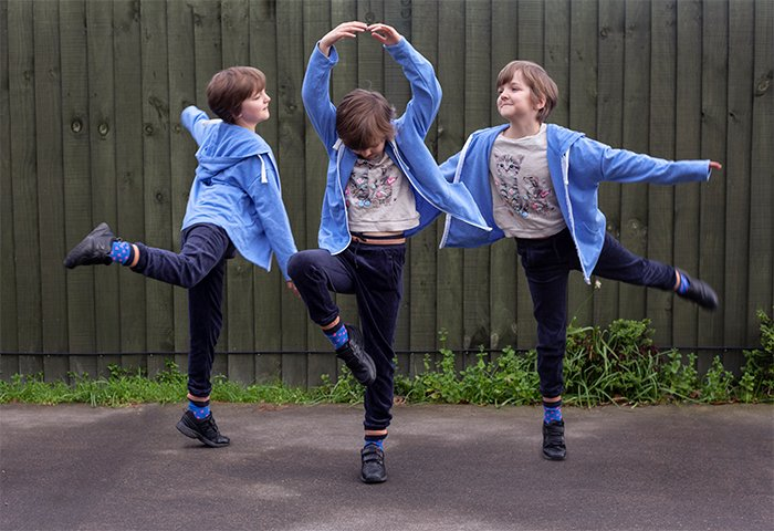 Multiplicity photography example of three of the same little girl dancing outdoors