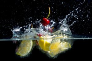 fruit photographed as it drops into water and creates a splash