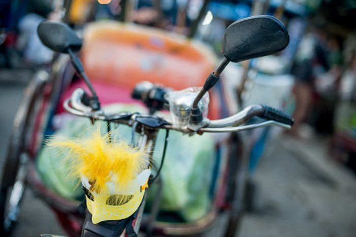 A yellow mask tied to the front of a samlar bike