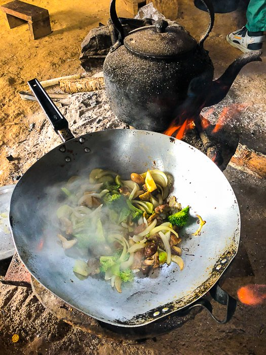 A pan of meat and vegetables cooking outdoors on an open flame